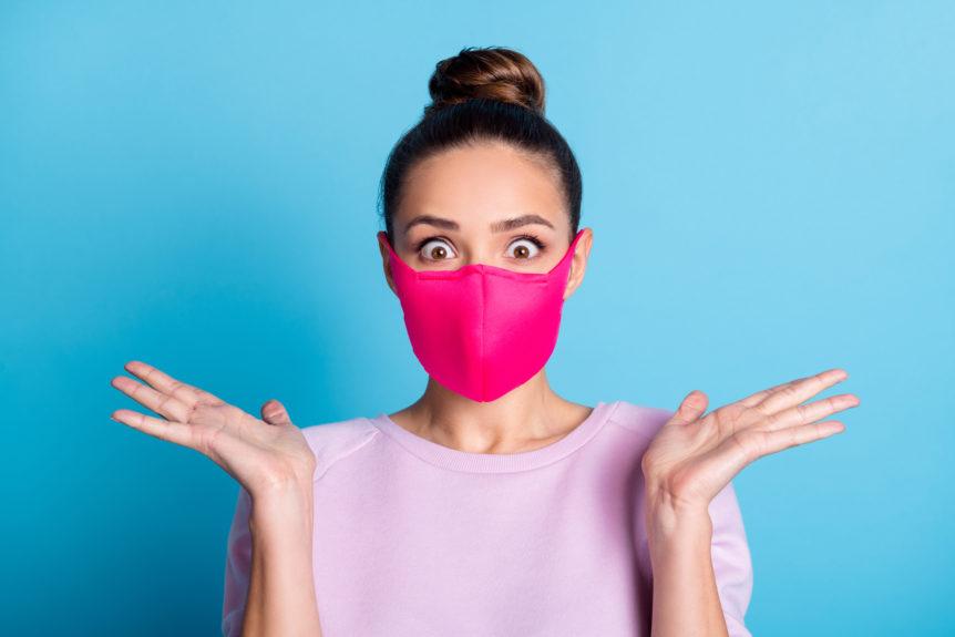 Überraschte Frau mit rosa Mundschutz vor blauem Hintergrund.