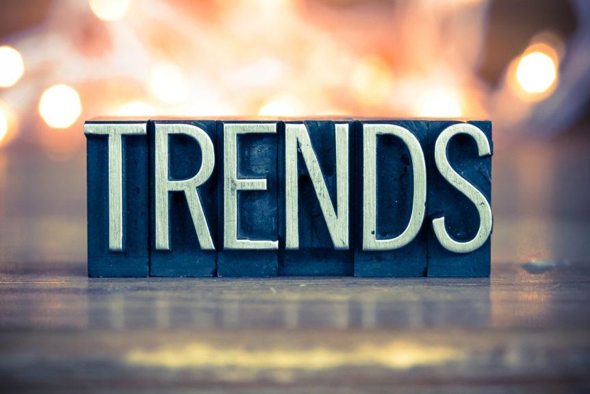 """Das Wort """"Trends"""" geschrieben auf Metallsteinen erscheint im Schweinwerferlicht."""