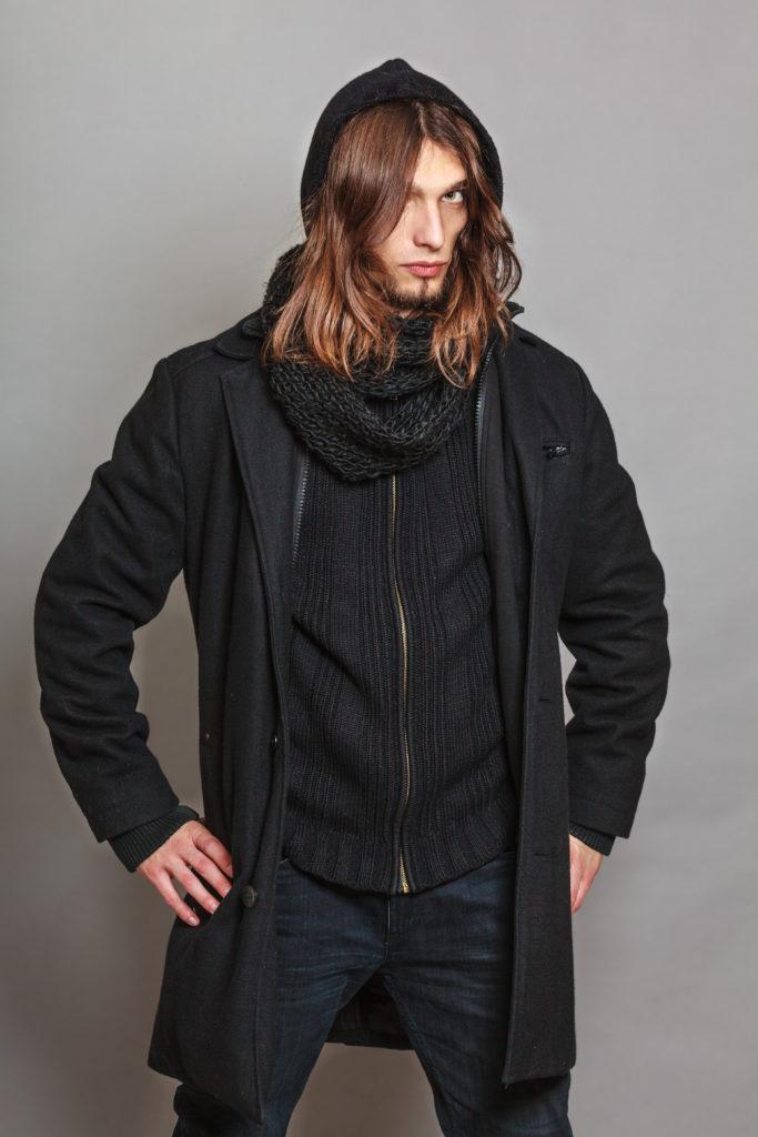 Mann trägt einen Mantel, dunkle Jeans, einen schwarzen Strickpullover und Schal.