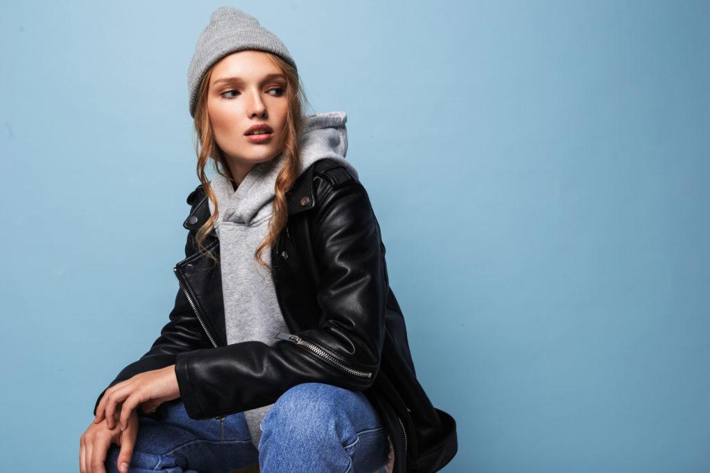 Junge Frau trägt einen grauen Kapuzenpullover, eine schwarze Lederjacke, Jeans und eine graue Strickmütze.