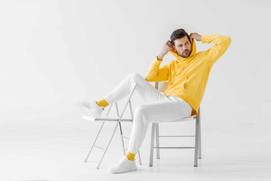 Mann sitzt lässig auf einem weißen Stuhl und trägt einen gelben Hoddie.