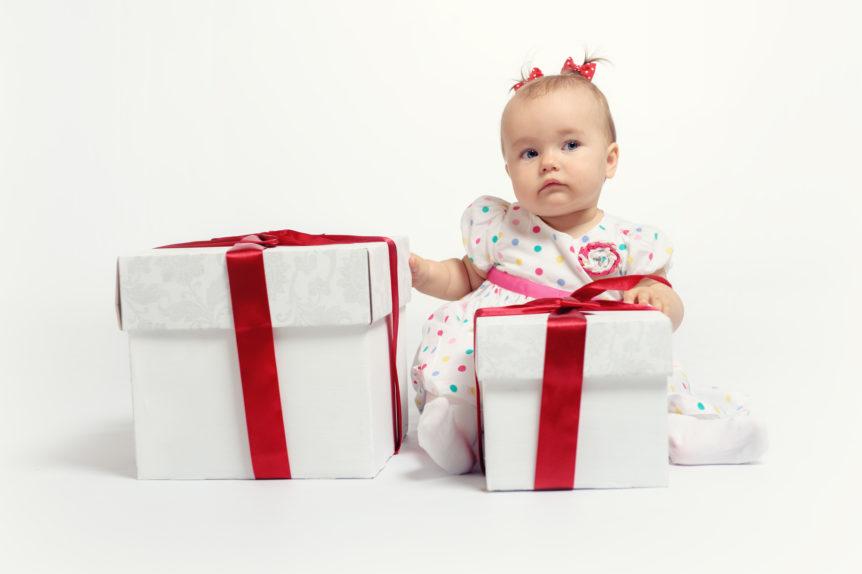 Kleinkind sitzt neben zwei großen Geschenken hinter einem weißen Hintergrund.