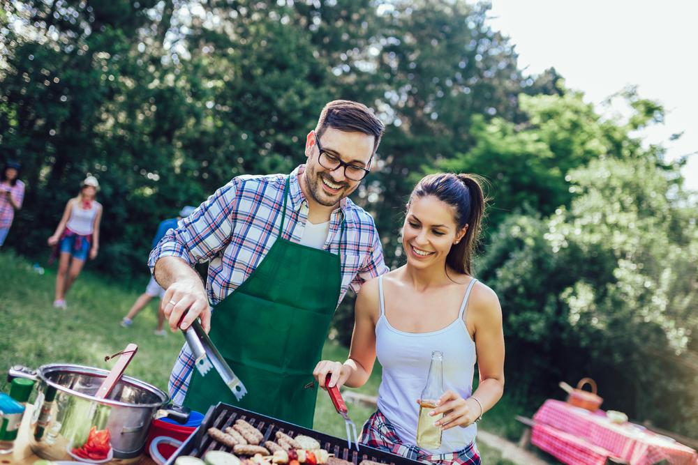 Junge Freunde grillen gemeinsam Fleisch und Gemüse und feiern eine Grillparty.
